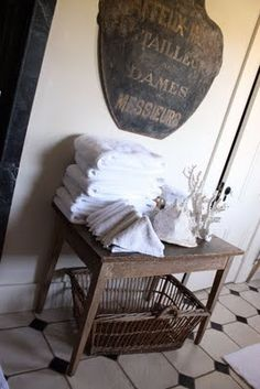 sarah anderson's pottery barn home, (where pottery barn shoots a lot of their photos) bath towels in triangles, basket, vintage sign <3 this vignette