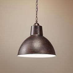 A contemporary industrial style pendant light with hammered bronze detailing and a warm bronze finish.
