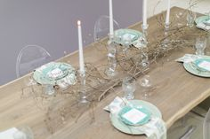 An Easter table with budding magnolia branches and clear candlestick holders