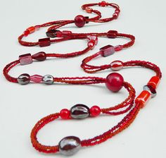 Long red necklace. 3 strand seed bead and glass bead necklace.