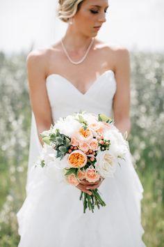 Peach and white bridal bouquet with eryngium thistle, peach hypericum berries and Juliet garden roses.  Flowers by Janie- Calgary Wedding Florist www.flowersbyjanie.com  Photo: @heartsparrow