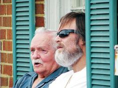 """Staff photo by Chris Fletcher Friends Vince Quillen of Portland, Tenn., and Charlie Jones of Whitehouse, enjoy a perfect """"window seat"""" for the parade in the facade of a downtown building. Jones said he's been coming to Mule Day off and on for about a decade and enjoys both the parade and the events at Maury County Park. """"Anything free is good when you're retired,"""" he said."""