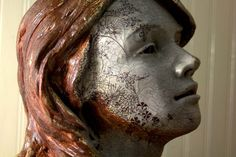 This is a ceramic sculpture bust of a woman. Hand scultpted in a stoneware clay, embellished with stencils, slips and underglazes. It was fired in a wood and soda kiln.  By Mudstuffing on Etsy.