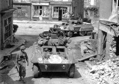 Two M8 Greyhound armored cars passing some destroyed French town