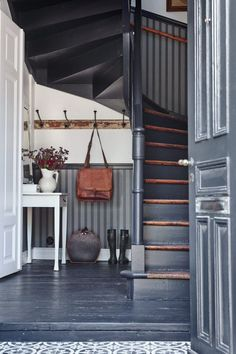 Unique entryway done in black stairs and rustic furniture |  Friday Favorites at www.andersonandgrant.com