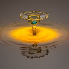 Yellow water drop forming crown with light blue dot in middle by RooM_the_Agency on 500px