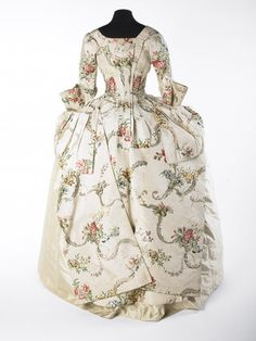 1746-1750 Open robe dress or mantua of white corded silk, brocaded with flower pattern in shades of brown, green, red and blue. The skirt is cut for wear over wide side-hoops and buttons over the hips.  Museum of London.