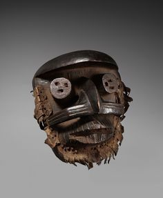 A GUERE/WE MASK  Liberia/Ivory Coast  The cylindrical eyes below the projecting forehead each with three rectangular holes, a horn like band to each cheek, the prominent mouth with incised grooves on the upper lip, hide about the border, dark glossy patina.  25 cm. high