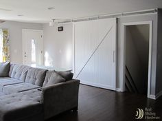 Sliding barn door alternately covers closet and basement openings.