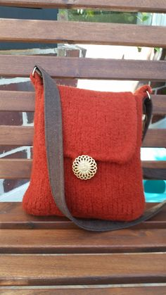 Red felted messenger bag is hand knitted then put through the felting process. It is made from 100 % wool and is completely seamless. It closes