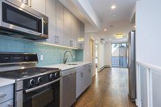 Beautiful open kitchen with quartz countertop, glass tile backsplash, Bosch and Samsung appliances in a duplex 3 bedroom garden home