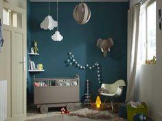 Peinture chambre enfant bleu canard rythmée avec les touches de couleurs taupe du lit enfant et des suspensions. Portes et fenêtres blanches jouent les contrastes colorés. Luxens