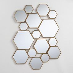 Make a grand statement with our contemporary panel featuring a cluster of brass hexagon-shaped mirrors in an array of sizes and depths for added dimension. Hang this piece horizontally or vertically to create the feel of art installation on any wall - an effect that's amplified when grouped in multiples.