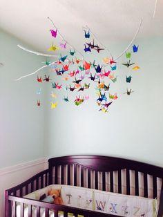 mobile pour bébé original - des brindilles blanchies comme base et plusieurs grues origami en papier coloré