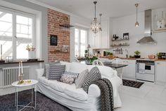 Zdjęcie:   biały salon skandynawski  na otwartej przestrzeni małego mieszkania ze ścianą z czerwonej cegły