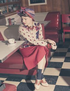 Woman is looking fierce at the diner. love the sweater and the shoes.