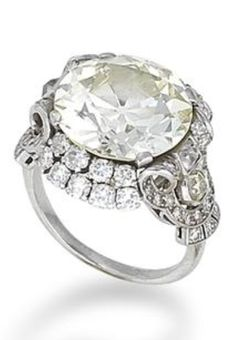 A diamond single-stone ring, circa 1935 The old brilliant-cut diamond, weighing 10.05 carats, between a double border of brilliant-cut diamonds, to a scrolling openwork gallery set with single and old brilliant-cut diamonds, remaining diamonds approximately 1.55 carats total.
