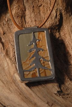 I hand cut the tree and soldered it to a bezel over a picture jasper. Hung from a leather cord.  Etsy.com/shop/foresthollow