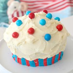 Recipe with video instructions: A GIANT cupcake to celebrate the 4th of July! Ingredients: Cake:, 1 1/4 cups cake flour, 1/2 tsp salt, 2 tbsp cocoa powder, 3/4 cup sugar, 3/4 cup vegetable oil, 1 large egg, 2 tbsp red food colouring, 1/2 tsp vanilla extract, 1/2 cup buttermilk, 3/4 tsp baking soda, 1 tsp white vinegar, Buttercream:, 2 cups unsalted butter, room temperature, 1 tsp vanilla extract, 5 cups confectioner's sugar, red and blue food colouring, red and blue candies