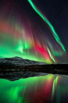 The aurora borealis over Høgtuva Mountain in Norway. The Earth's magnetic field funnels particles from the solar wind over the polar regions. More than 80 kilometres above the ground, these collide with molecules in the atmosphere causing them to glow: green and pale red for oxygen and crimson for nitrogen   Photograph: Tommy Eliassen/Royal Observatory