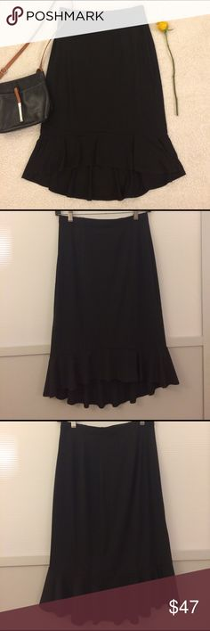 Tadashi Collection Black Ruffle Skirt Classic black midi skirt by Tadashi. High-low with a ruffle hem accent. Material is silky and very stretchy. Waist is about 13.5 inches (but stretches quite a bit). Length of front is about 23 in, back is about 27 in. There is one small defect- on the waist band there are a few small dents from a faulty hanger, but they are hardly visible. Otherwise excellent condition! Tadashi Shoji Skirts Midi
