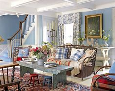 Gorgeous eclectic living room! Soothing blue and white toile window treatments, rustic blue coffee table/bench, blue and white plaid pillows, rattan sofa?, white tray ceiling