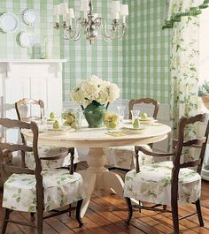 White painted table, brown chairs with skirts, plates as wall art