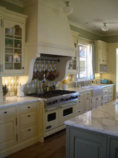 kitchen by brooke gianetti of velvet and linen.  love the lemon yellow range, the painted cabinets, and retro light fixtures.  the tile backsplash makes me swoon.