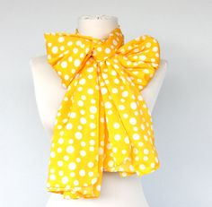This is a satin, very soft polka dot scarf in yellow. It has a bright yellow color with white polka dots on it. It is perfect for summer or