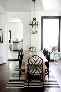 Monochrome dining room. White walls, black painted bamboo chairs, natural timber table, black and white stripe area rug, lantern light fitting.
