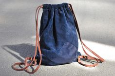 blue suede backpack with brown leather straps