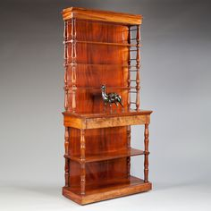 A Empire Etagere : Nicholas Wells Antiques An unusual Charles X flame veneer mahogany open bookcase. With four shelves above a frieze drawer and two below. Each shelf is supported by turned baluster columns with ornamental collars. In the manner of Jacob.