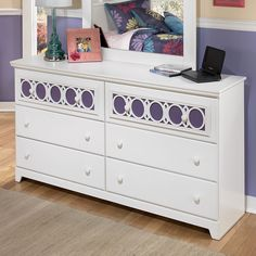 "With a bright replicated white paint finish flowing cleanly over the decorative ""Egg and Dart"" lattice accents, the Zayley Dresser by Signature Design by Ashley Furniture offers an exciting contemporary design that features the versatility of 9 interchangeable color panels to add you own personal flair to the bedroom decor. Bring the Zayley Youth Collection into your home today for quality pieces that both you and your child can enjoy!"