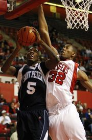 Tim Larsen/APSt. Peter's College's Jeron Belin, left, gets pressure from Brian Okam of Rutgers while shooting during the first half of an NCAA college basketball game in Piscataway. In what was expected to be a competitive game, Rutgers (9-2) demonstrated...