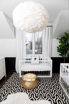 This modern nursery uses a simple black and white palette with touches of gold to really make a space that is high impact. Lucite cribs layered with bold patterns and a statement light to soften things up makes this a total dream twin nursery.