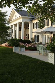 White house with black shutters, columns, patio