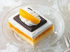 Unterhalb der Pudding- und Sahneschichten verbergen sich leckere Pfirsiche auf einem Biskuitteig. Getoppt wird dieser Kuchen von knusprigen Butterkeksen.