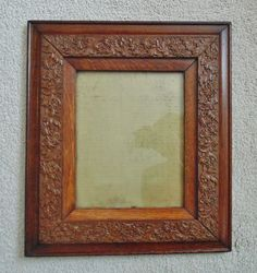 """antique Arts & Crafts picture frame. Oak wood and decorative gesso designs of flowers and leaves. The frame measures 16 1/2"""" x 14 1/2"""" and holds a picture measuring 8"""" x 10"""". There is some crackling to the gesso, which is to be expected in a frame of this age. Very little loss to the frame. There is a 1"""" sliver chip to the upper left of the outer frame."""