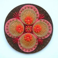 Felt applique brooch that resembles penny rug style.