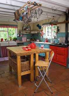 Red AGA with teal kitchen: love the bold contrast!