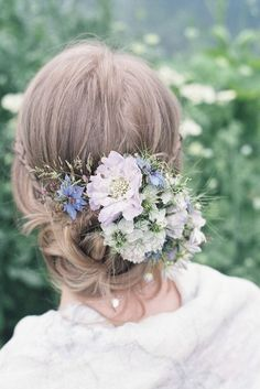 braided and twisted messy updo with lots of fresh blooms