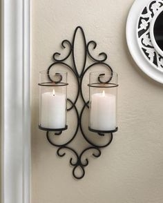 Light up your wall with gorgeous glow that will shimmer and shine with everlasting style. This beautiful iron wall sconce features two clear hurricane lanterns