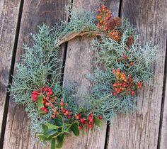 木の実がアクセントになった素敵なリース。 コニファー(「ブルーアイス」)の基本のリースに、「クリスマスホーリー(セイヨウヒイラギ)」、「ローズヒップ」、松ぼっくりをあしらっています。