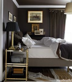 In a house full of boys: Masculine Interiors: How to mix dark neutrals: Annie Brahler - Chic bedroom with chocolate brown walls paint color, black leather tufted headboard with gray linen bed, chocolate brown shams, antique brass etagere nightstand, antique brass lamp with black shade and chocolate brown curtains. House Beautiful via Decor Pad.
