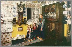 Vrouw poseert met twee kinderen in Marker interieur. O.a. Friese staartklok (bruidsklok met latoenkoperen rand rond de wijzerplaat en houtsnijwerk), verder een Assendelftse kast met beschildering van bijbelse voorstellingen. 1955-1980 #NoordHolland #Marken