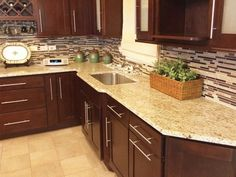 Giallo Oremental Countertop Brown Cabinets Tile Flooring Glass Tile  Backsplash
