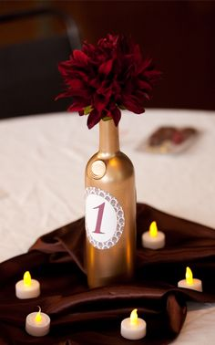 wine bottle table number... Paint a glossy navy blue color and put one yellow peony in each. Surround with real tea candles