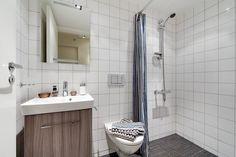 petite salle de bain avec un carrelage mural blanc, aménagée avec un meuble sous-vasque en bois et une douche à l'italienne avec rideau Bathroom, White Wall Tiles, Brown Bathroom, Washroom, Full Bath, Bath, Bathrooms