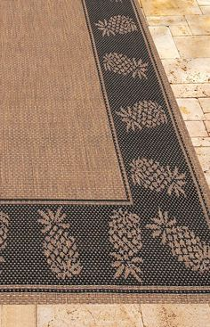 Our Oasis Retreat Indoor/Outdoor Rug features a solid center panel, artfully surrounded by a pattern of pineapple outlines. Distinctively designed to complement classic outdoor decor, this versatile floor covering is ideal for patios, entryways, and sunrooms.