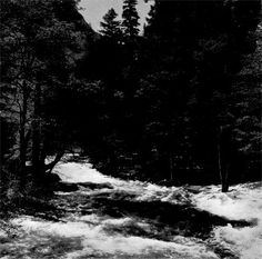 At Happy Isles the Merced River in a noisy, playful mood, rushes in white-crested foam past rocky islands. by Ansel Adams